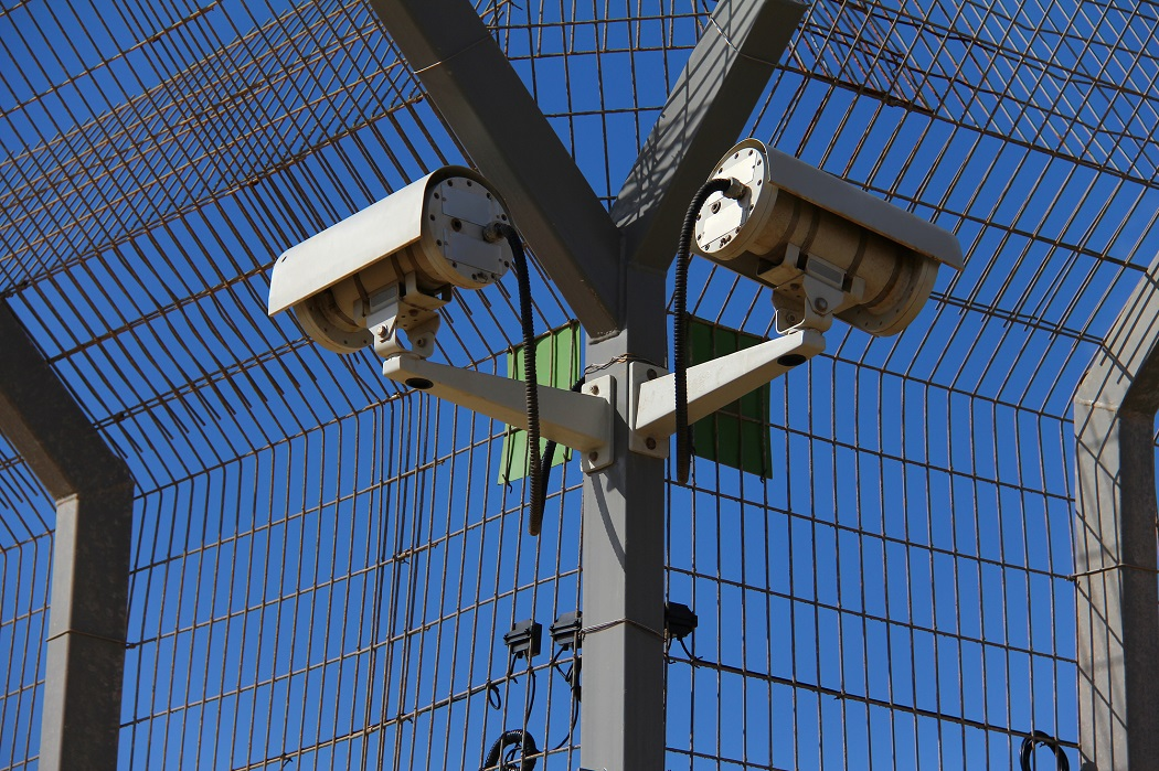 A secured industrial zone with Security camera on blue sky background